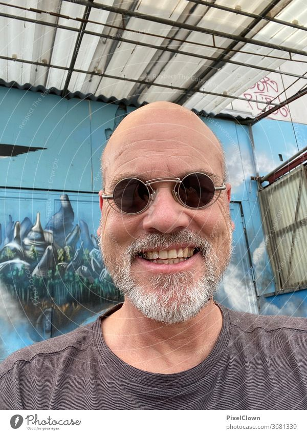 old man in blue Man Only one man portrait Adults Sunglasses Bald or shaved head Face Graffiti Wall (building) Facade Blue Facial hair Laughter