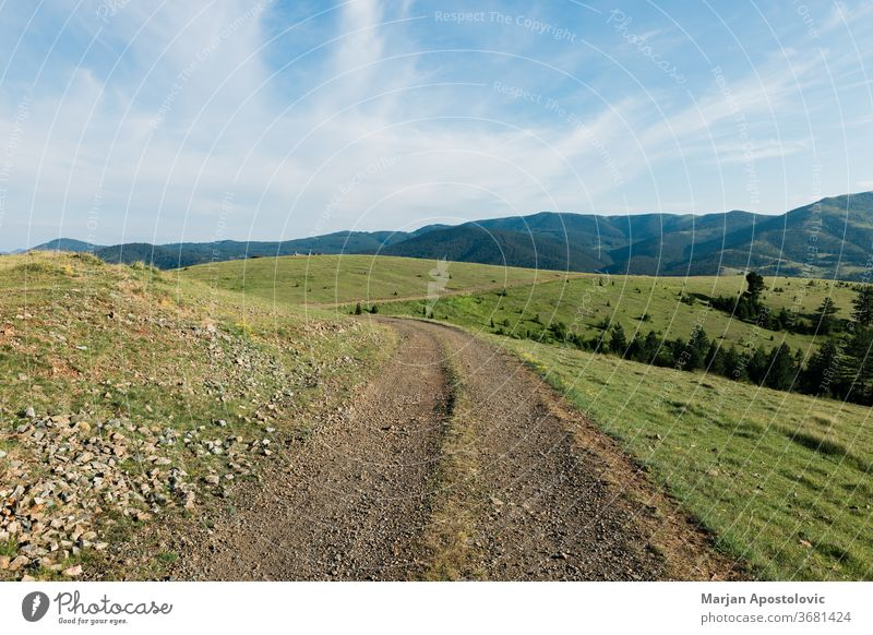 Dirt road in the mountains in sunny day background beautiful blue clouds country countryside dirt environment exploring field grass green hiking hill hills land