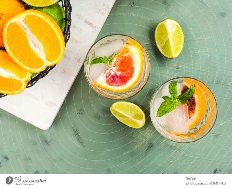 Fresh summer citrus drink with ice on green water cocktail lemonade detox mocktail blood orange fruit flat lay top view lime juice mint soda infused sweet