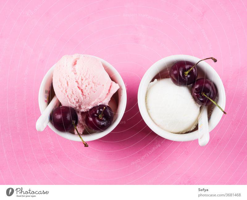 Two ice cream cups with cherries on pink strawberry scoop ball gelato red cherry berries yogurt summer sundae sweet fruit temptation topping food frozen garnish