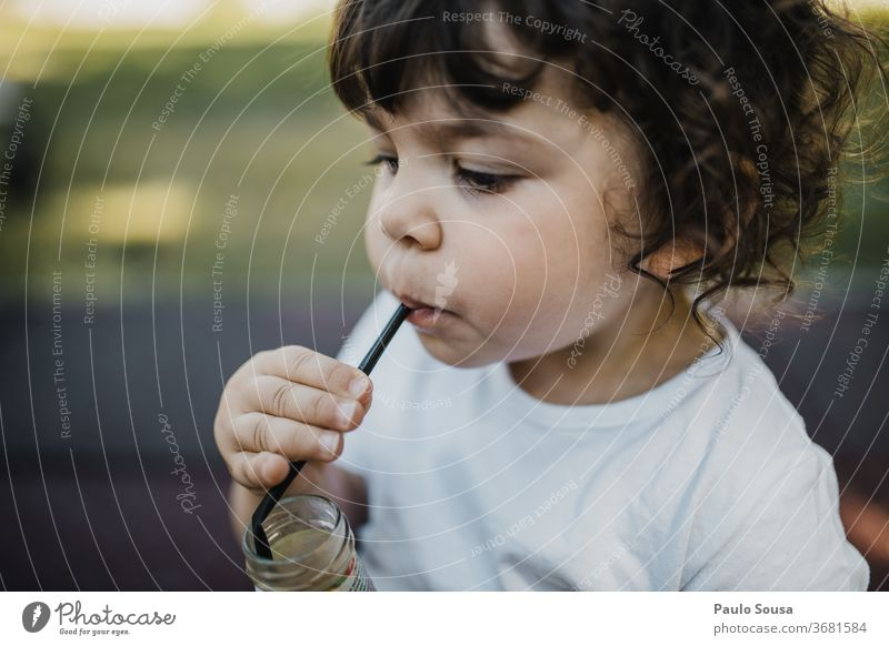 Child drinking Juice from straw Straw Nature Yellow childhood Drinking Juice glass Fresh Healthy Lemonade Colour photo Beverage Cold drink Fruit Delicious Food