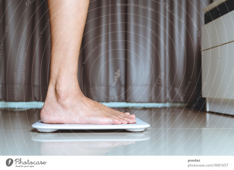 Female leg is standing on white scales at home anorexia background balance bathroom beautiful beauty bmi calorie calory caucasian control detail device diet