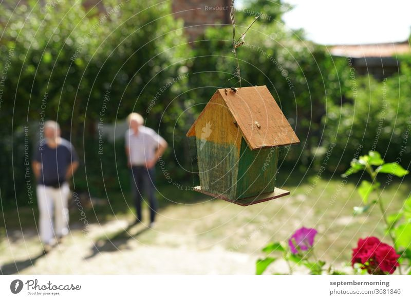Bird house from behind, hanging Bird house made of wood 2 men unsharp in the background Summer in the garden red flower in the foreground Pastel shades