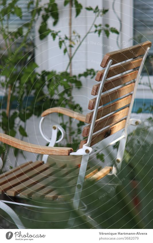 Garden chair made of wood and metal with tomato plant on the house wall Chair Colour photo Calm Furniture Outdoor furniture Resting point