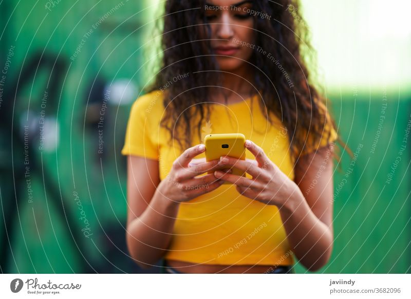 Young Arab woman walking in the street using her smartphone arab young texting message close-up typing yellow copyspace girl recording hairstyle attractive