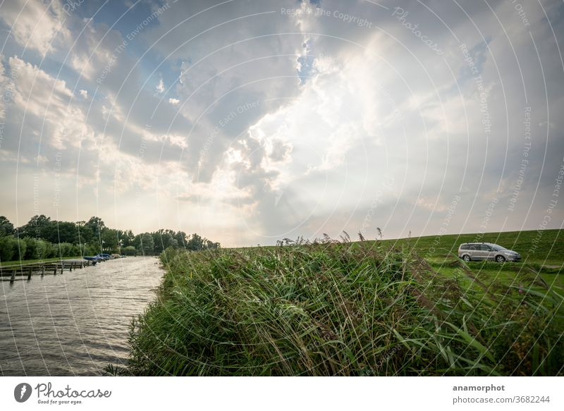 Canal with reeds against the light behind the Ijsselmeer dike Water Clouds in the sky met rays godrays Colour photo Deserted Exterior shot Sky Day Blue Nature