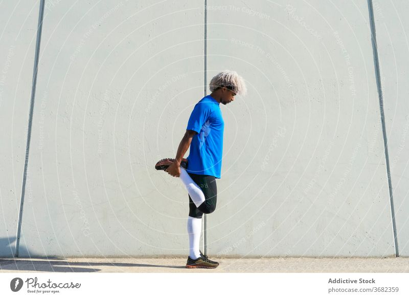 African American athlete warming up on street sportsman warm up exercise fitness stretch workout building city wall male healthy modern legs training