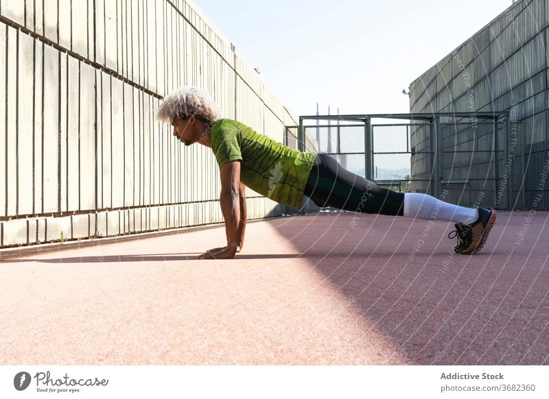 African American sportsman doing push ups on street city fitness workout enclosure exercise physical male training wellness strong lifestyle power plank healthy