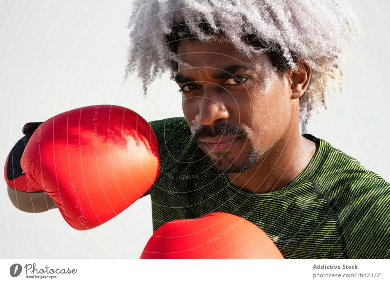 African American boxer ready for training sportsman stance guard serious street wall shabby male workout boxing power black ethnic african american athlete