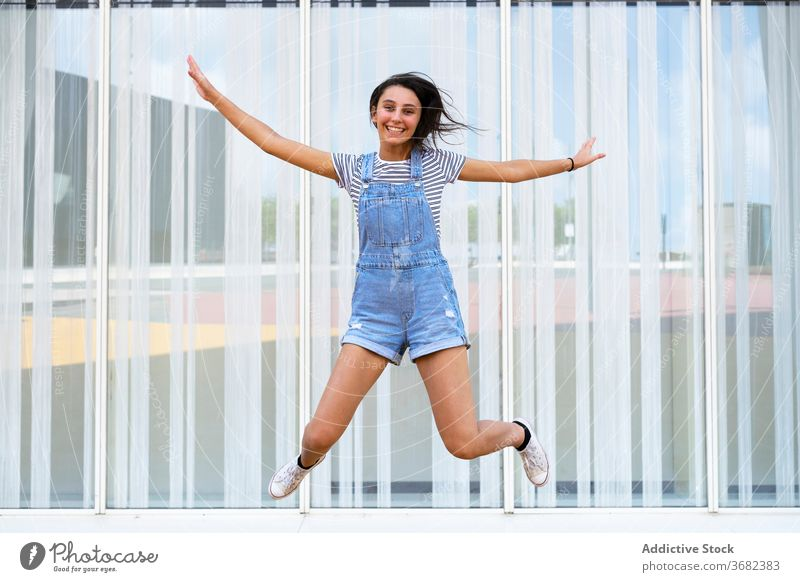 Happy teen girl jumping near glass wall smile happy casual leap fun excited building joy glad optimist modern delight teenage positive moment millennial
