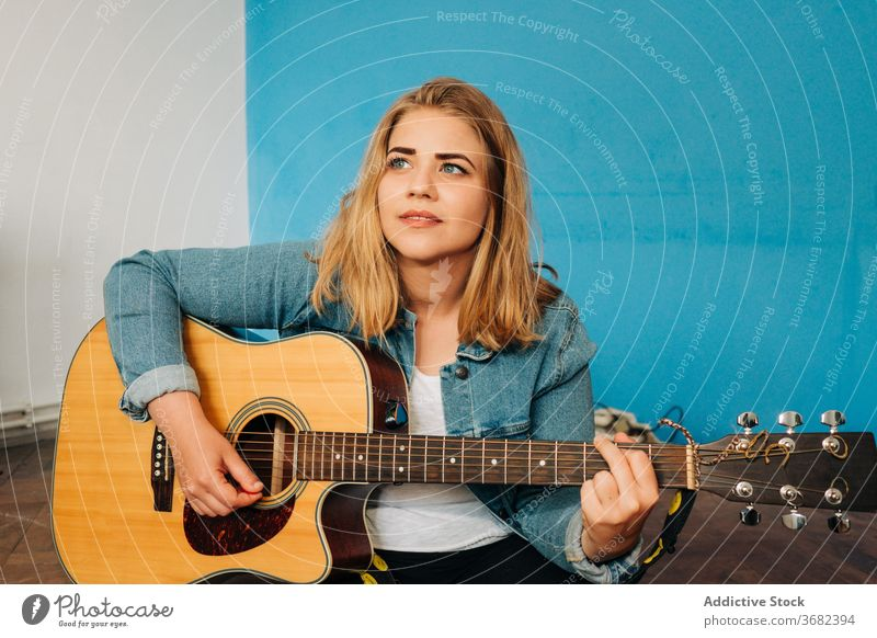 Pensive woman playing guitar on floor thoughtful musician wall acoustic young female casual instrument sit song melody think pensive sound happy hobby perform