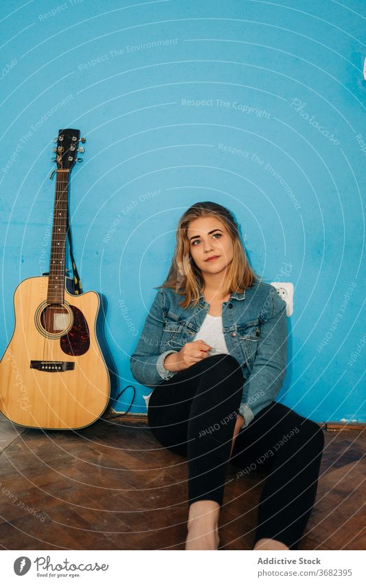 Pensive woman sitting near guitar on floor play thoughtful musician wall acoustic young female casual instrument song melody think pensive sound happy hobby