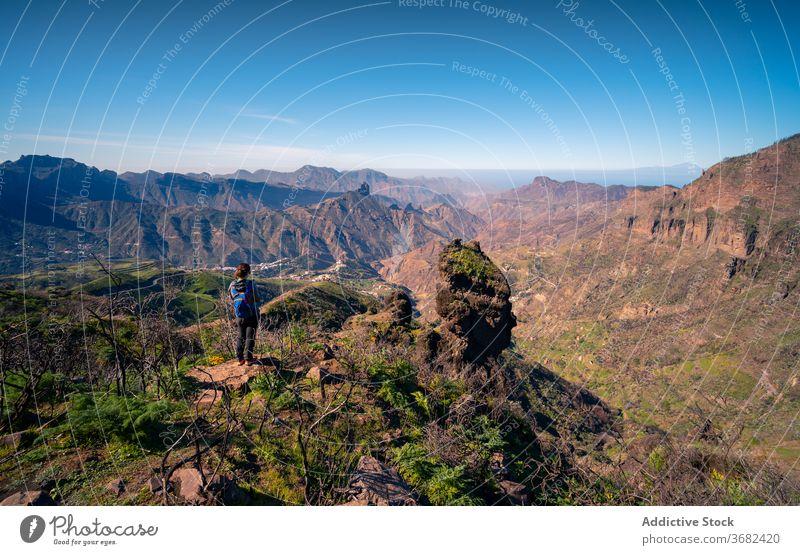 Traveler on high peak in mountains highland rock traveler hill admire enjoy woman rough stone rocky gran canaria spain tourist breathtaking amazing nature