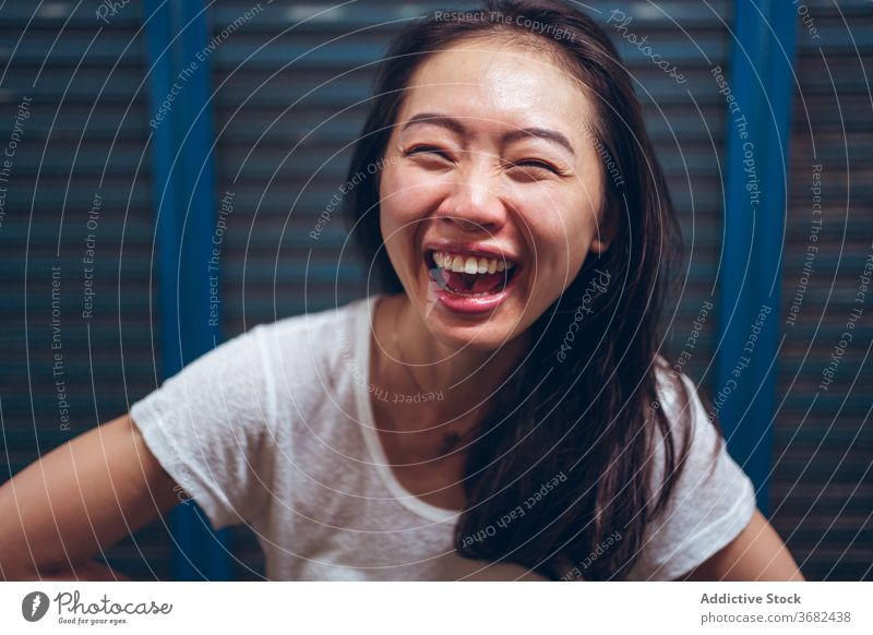 Cheerful young ethnic woman laughing at camera cheerful happy delight having fun excited positive portrait asian glad female casual optimist modern content