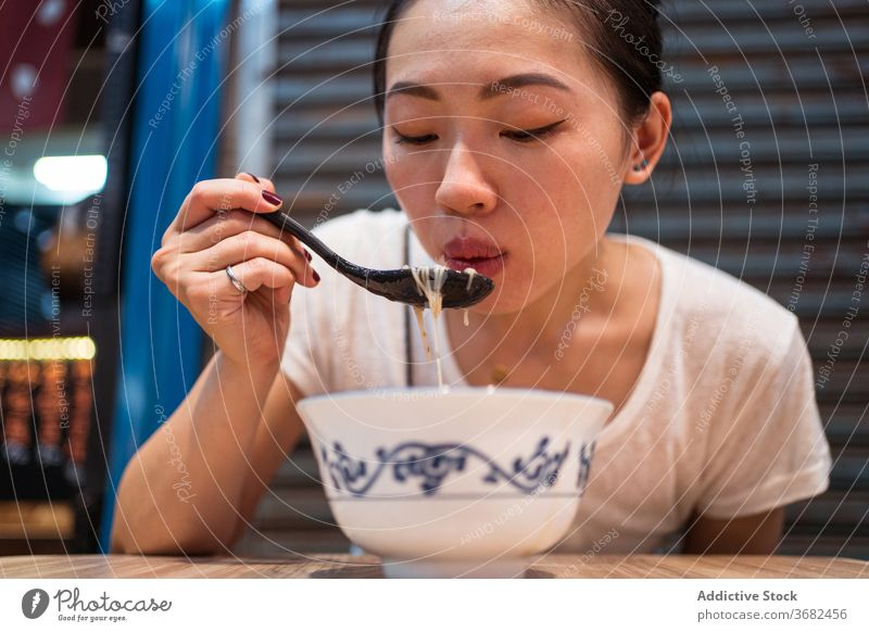 Asian woman eating traditional noodles soup taiwan asian food bowl young meal female ethnic lunch tasty dish lifestyle cuisine yummy hot blow oriental enjoy