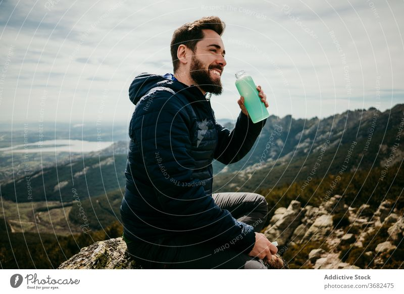 Happy male traveler drinking water in mountains man smile rest boulder puerto de la morcuera spain cheerful fresh bottle overcast sky vacation lifestyle sit