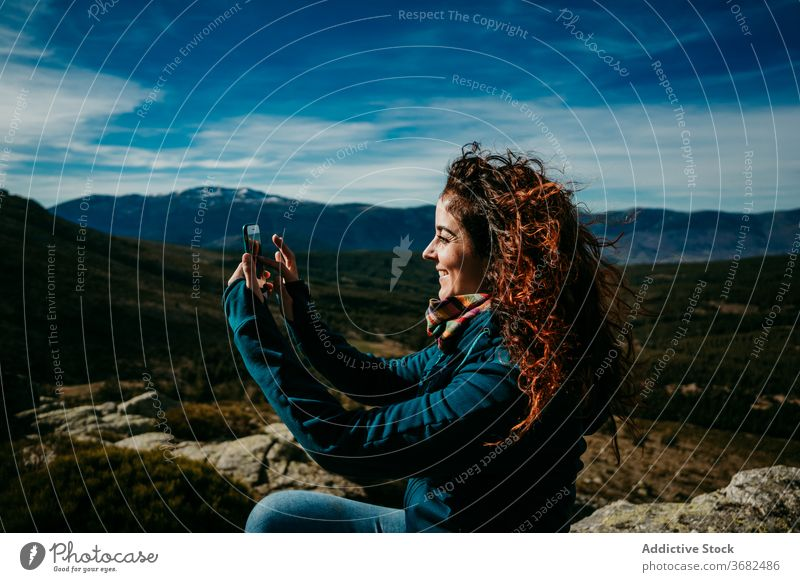 Positive female hiker shooting mountains woman smartphone take photo trip countryside smile ridge puerto de la morcuera spain cloudy sky device gadget relax