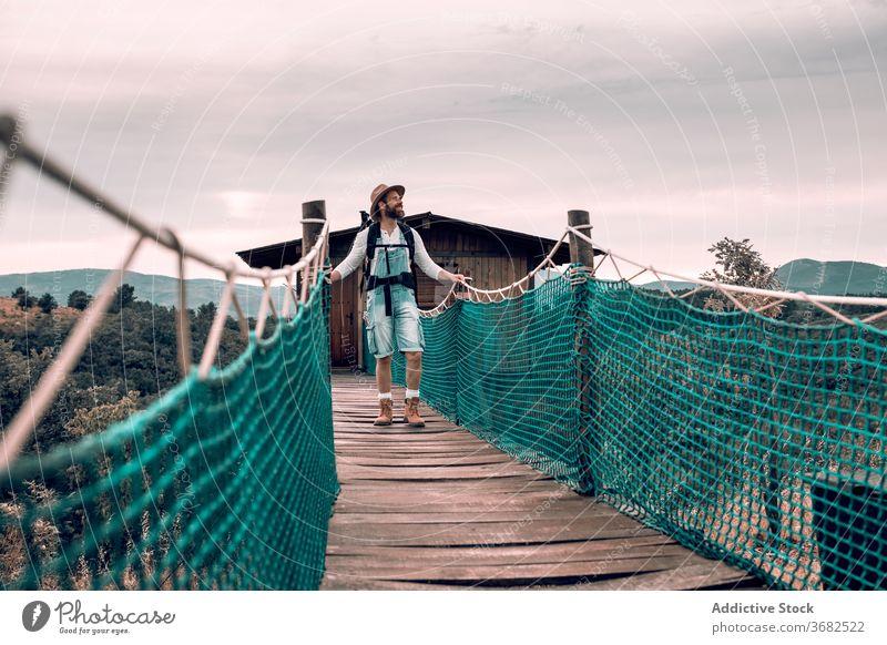 Traveling man walking along wooden footbridge suspension tourist backpack admire landscape vacation male adventure trip tourism content journey traveler young