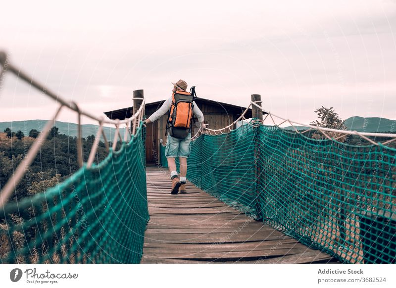 Anonymous traveling man walking along wooden footbridge suspension tourist backpack admire landscape vacation male adventure trip tourism content journey