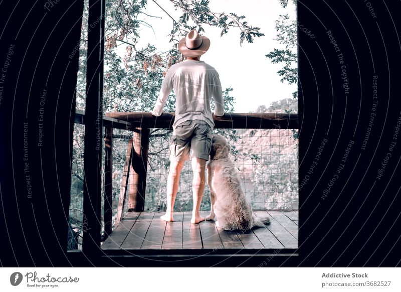 Relaxed man on balcony with dog forest morning house traveler enjoy wooden vacation male summer friend freedom terrace tourism idyllic relax animal holiday guy