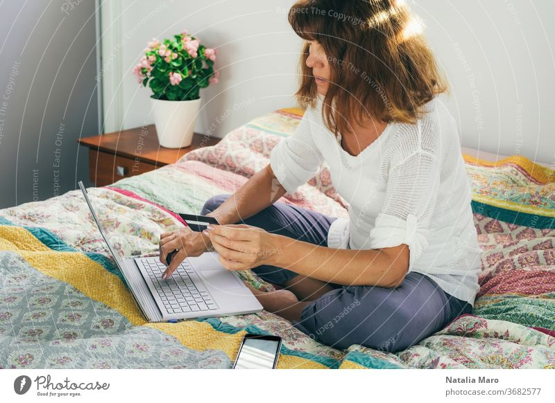 Woman paying by card for shopping online from home on a laptop, sitting on the bed. woman buy purchase middle aged activity bedroom business care caucasian