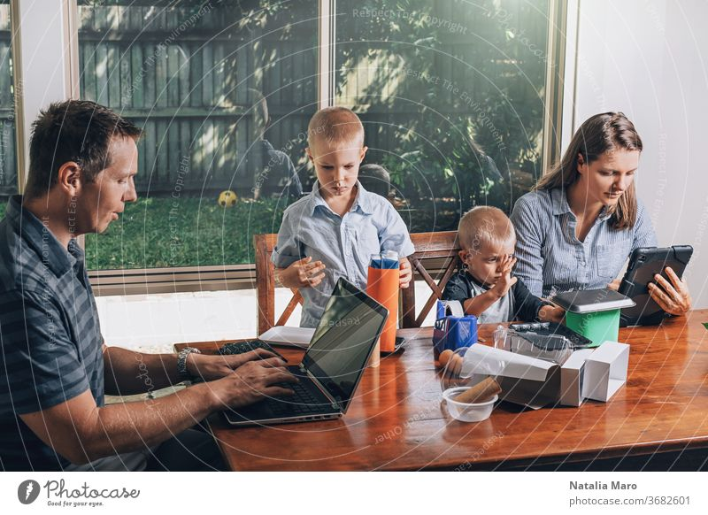 Concept of work from home and home family education. Parents and two sons are sitting at the desk. parent laptop kid office recycled craft business child