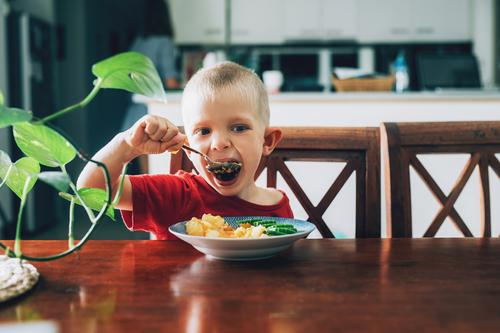 Cute child, preschool boy, eating veggies for lunch in the dining room kid childhood food happy spoon mouth cucumber potato hungry vegetable joy caucasian