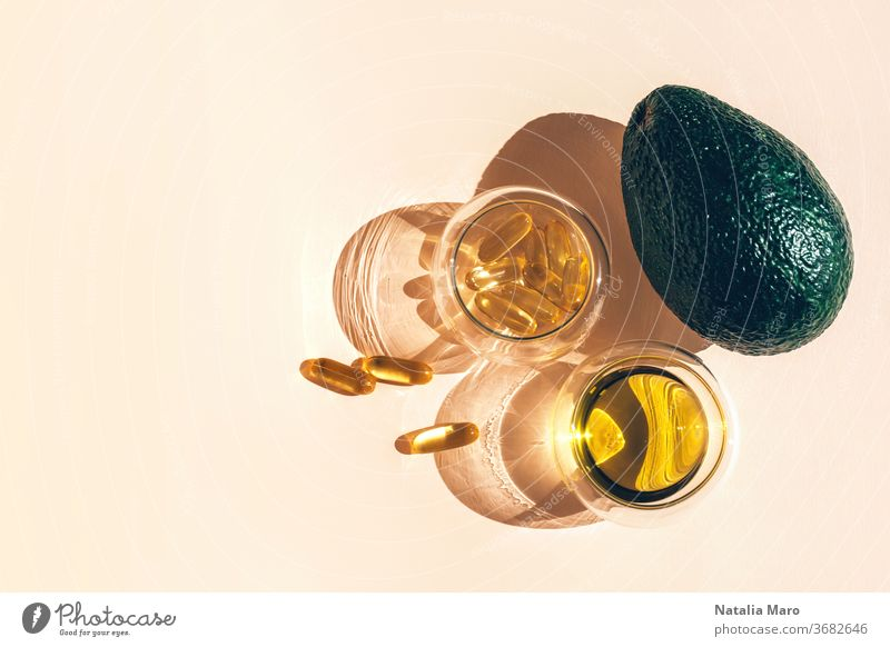 Capsules fish oil omega-3 in glass cups and an avocado with a shadow in the sunlight on the beige background. pharmacy capsule pill supplements medicine tablet