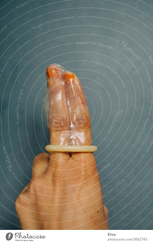An unrolled condom on two fingers. Topic sexual intercourse and contraception. prevention Condom feminine woman's business go along with by hand Protection