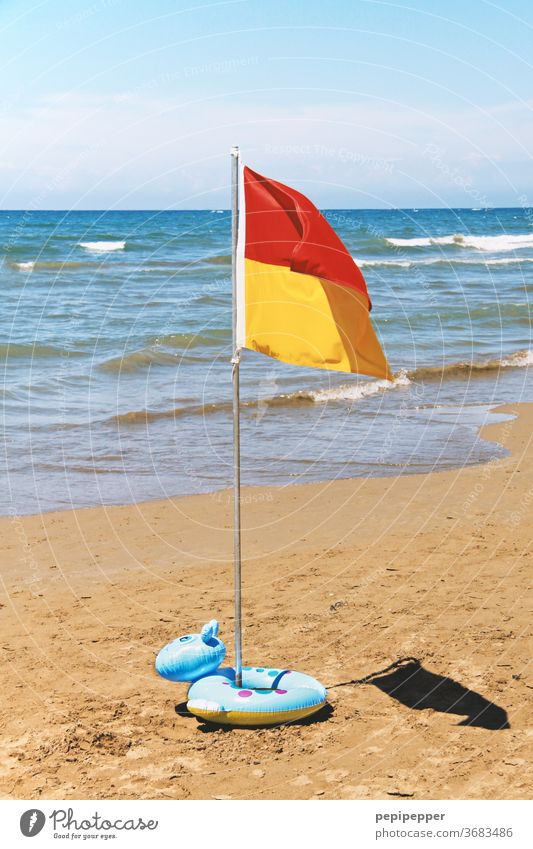 Flag on the beach with swim ring Beach Ocean Sand Water Waves Sun Sky Coast Summer Vacation & Travel Blue Tourism Summer vacation Beautiful weather Deserted