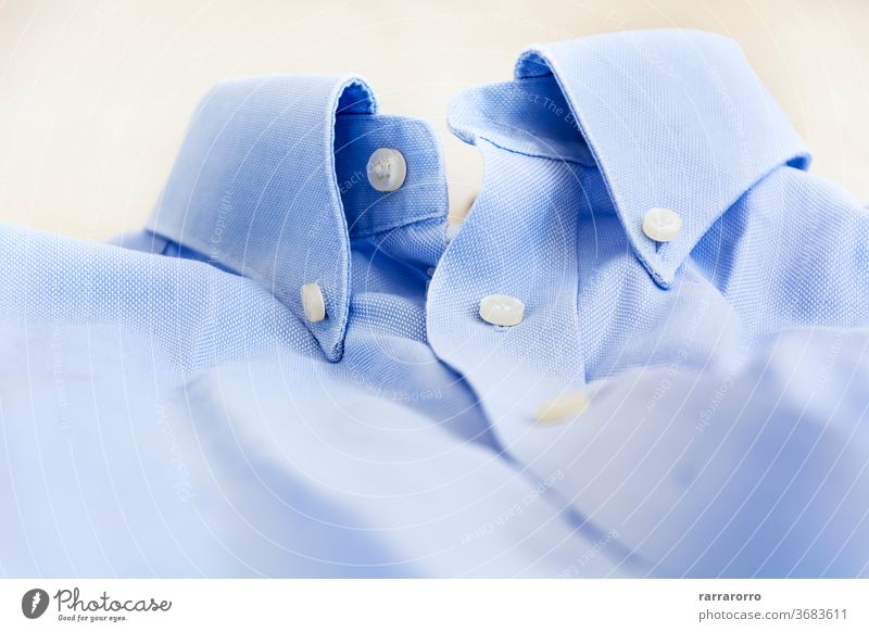 A light blue shirt with a button down collar. cotton dress fashion man clothing clothes business textile clean closeup nobody style white background garment