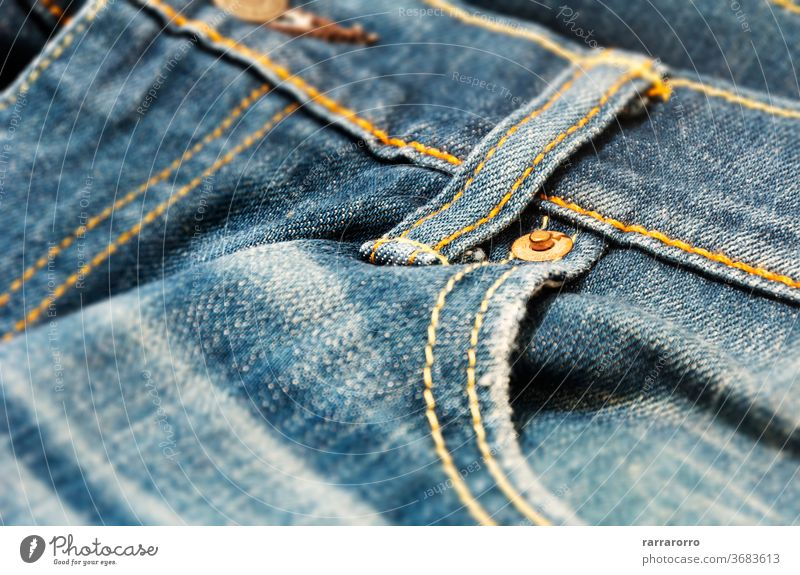 close-up view of the copper rivet on the pocket of a pair of denim trousers jeans canvas fabric texture blue fashion clothing clothe design pattern material