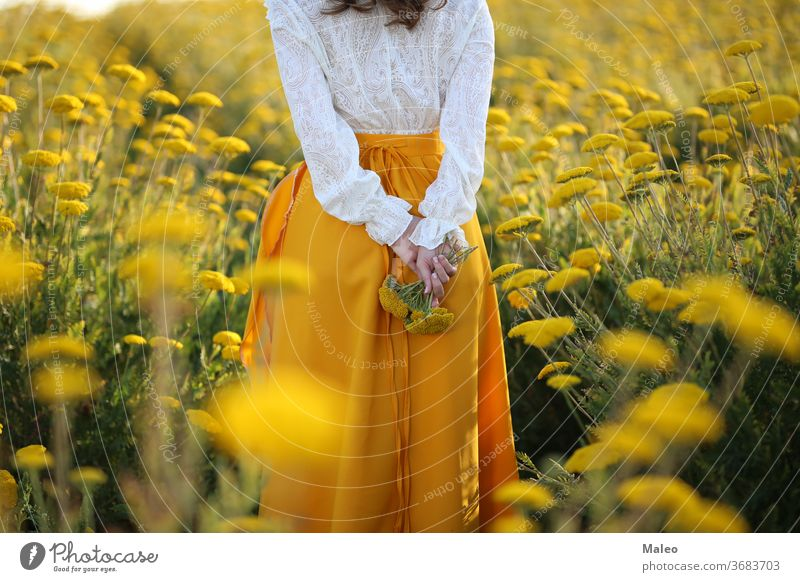 A girl in a yellow skirt and a white blouse stands in a field of yellow flowers background bohemia country couple dusk fingers grass green height hills loft