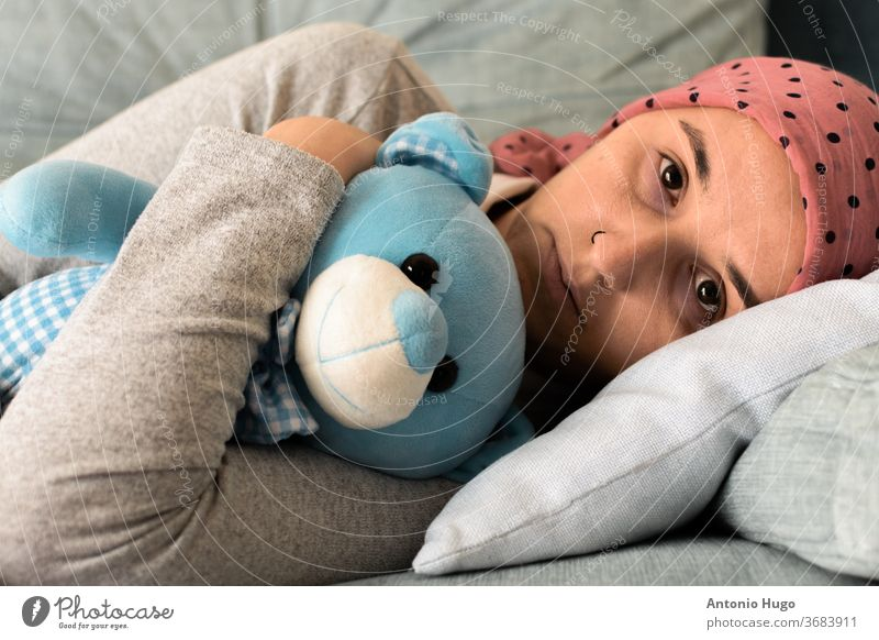 Portrait of a woman with cancer and depression locked in her home thinking. Pink headscarf. Lying on the couch with her blue teddy bear. Fighting cancer.
