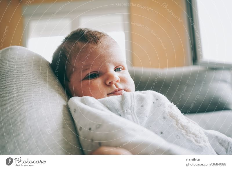 Lovely newborn baby girl with a warm pajama at home cute adorable funny boy kid daughter son face expressive expression growth upbringing nurture skin issues