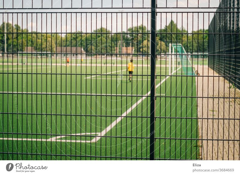 Young footballer on a football field behind a fence soccer soccer field Football pitch Sports Playing Sporting grounds Fence Ball sports Leisure and hobbies