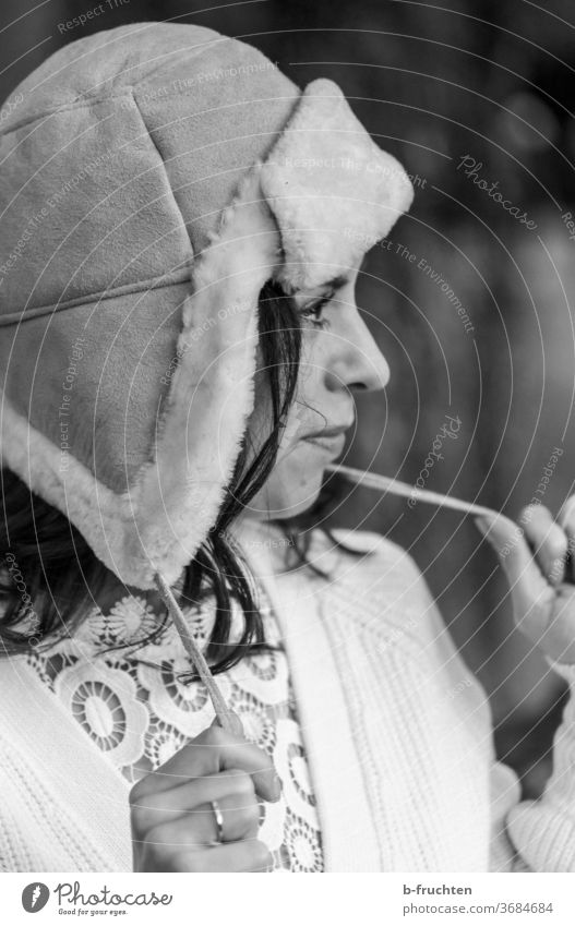 Woman with winter cap, looking ahead, black and white portrait Winter chill Human being Face Adults Exterior shot Head Looking Future at the front hands stop