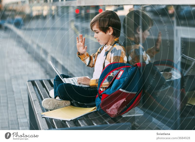 A cute boy is sitting on a bench, holding a laptop on his lap, next to a backpack. The boy communicates with friends using the computer, waving to them. Education, technology, distance learning