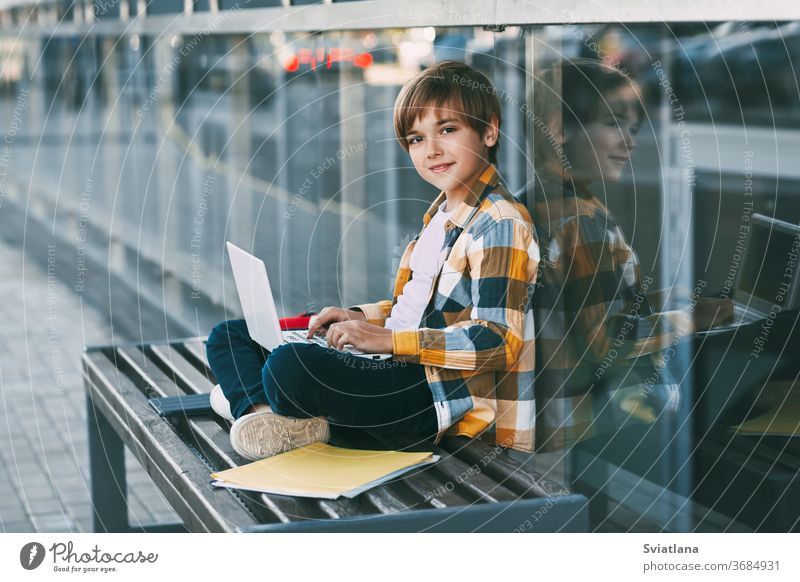 A cute boy in a plaid shirt is sitting on a bench with a laptop and typing on the keyboard, next to a backpack. The student is preparing for outdoor classes
