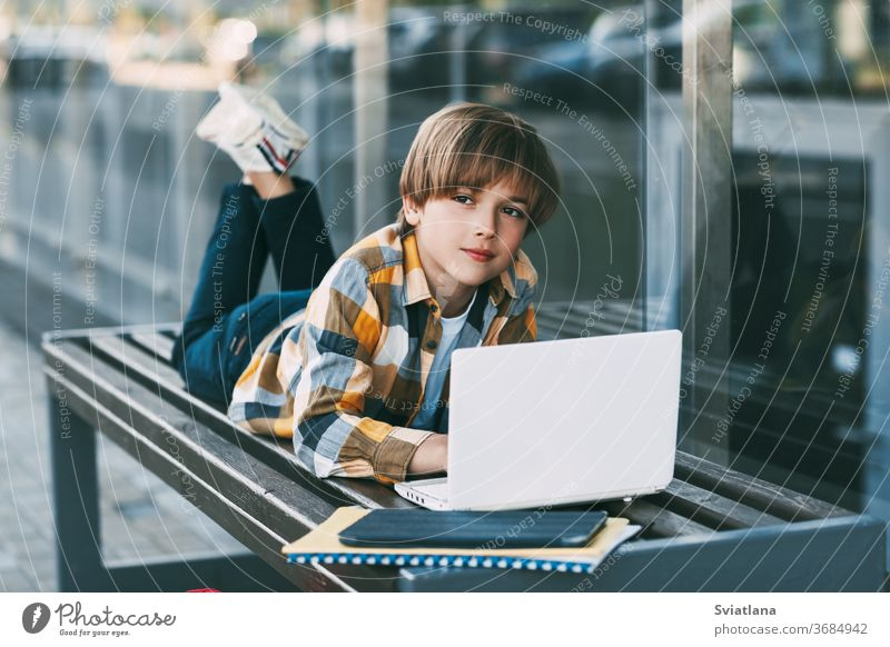 A smiling boy is lying on a bench and preparing for school lessons, next to a backpack. The boy is resting between classes. Social distance. Distance learning, education, modern technologies
