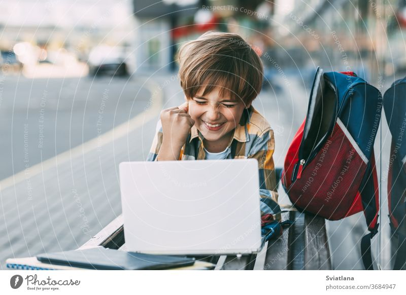 A cheerful boy is lying on a wooden bench and working on a laptop, next to a backpack. A student prepares for school lessons using the Internet. Social distance. Distance learning