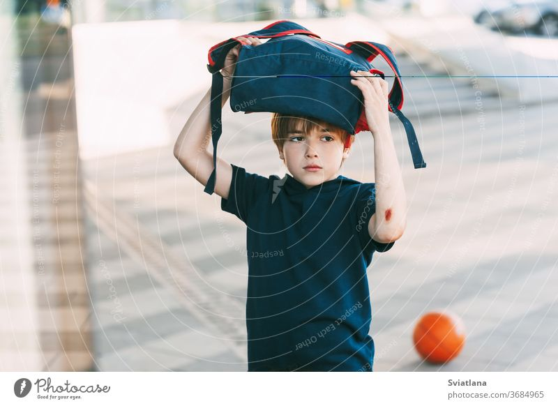 A tired boy in sports uniform and with a wound on his arm returns home after basketball training. Education, upbringing, physical education backpack smile