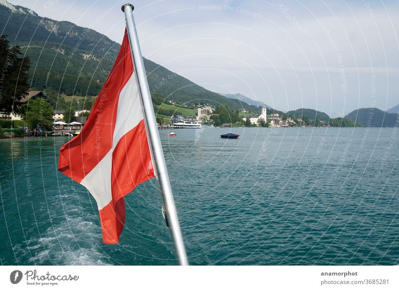 Austrian flag on the boat with view to Wolfgangsee Lake Wolfgang sheep's mountain Church Colour photo Exterior shot Mountain Alps Sky Beautiful weather