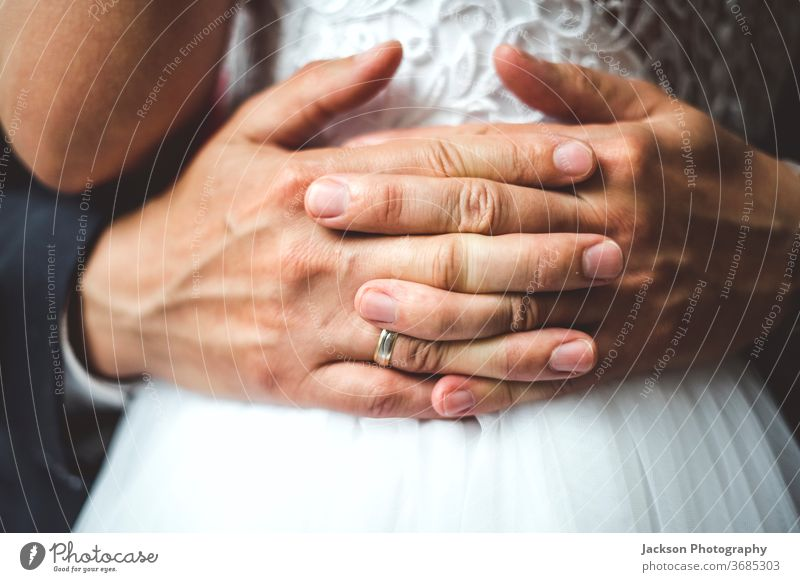Close up of groom's palms embracing bride. ring wedding embrace close up waist hug detail fingers concept hand newlywed emotions caucasian lifestyles marriage