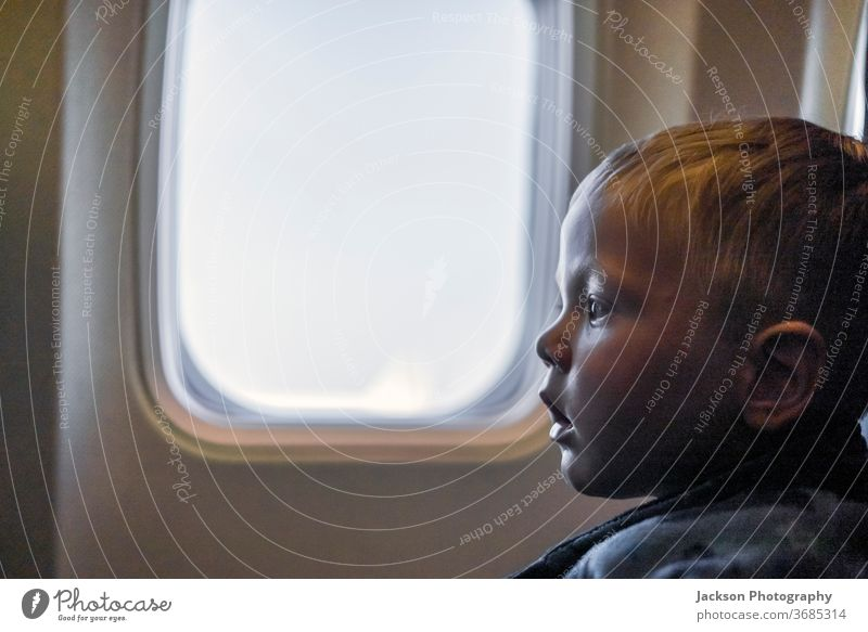 Serious toddler sitting next to the window in the airplane kid serious travel boy copy space uncertain scared curious small caucasian face view indoor concept