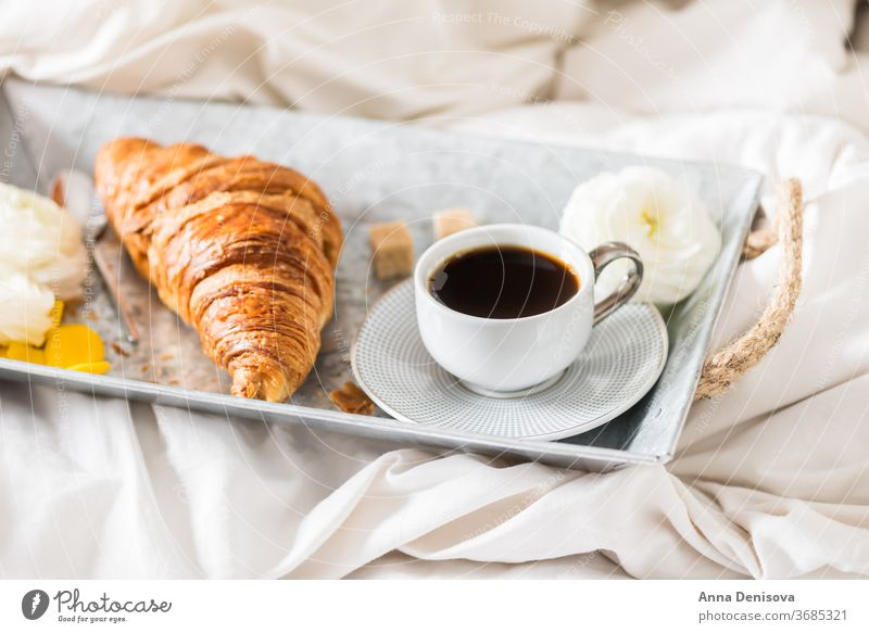 Fresh Croissant, Cup of Coffee and Ranunculus Flowers. Breakfast coffee croissant breakfast in bed morning romance pastry cup white table ranunculus flowers