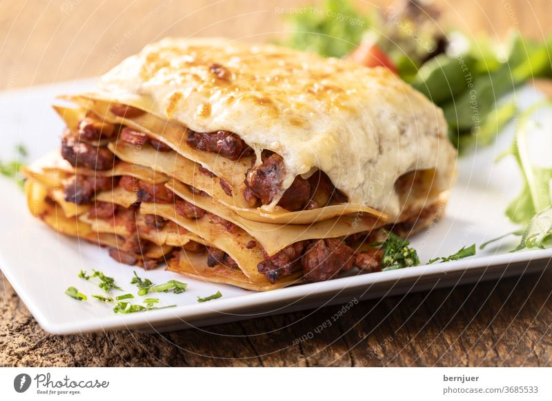 Close-up of a portion of lasagne Lasagne Rustic Tasty nobody homemade Delicious Crockery Mozzarella bechamel Chop Bolognaise Meat Nutrition Mediterranean Meal