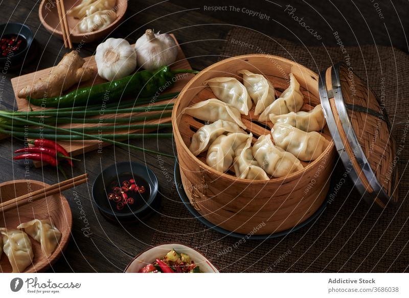 Chinese steamed dumplings xiaolongbao jiaozi chinese food yummy wood dark food vegetables salad cucumber foodie tradition traditional Asia Asian food chopsticks