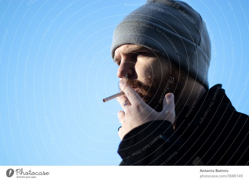 Caucasian bearded male with a beanie holding a cigarette, harshing sunlight with strong shadows.  Narrow shot with blue sky background addict addicted addiction