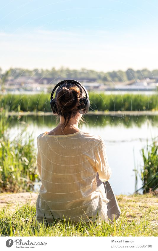 Woman with headphones is meditating, sitting in front of the river,  just after the sunrise. adult beautiful beauty body calm caucasian concentration energy